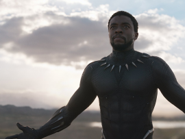 King T'challa wearing the Black Panther suit without his helmet stands with his arms stretched wipe open, looking upwards