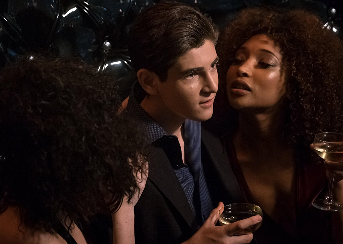 An underage Bruce Wayne is surrounded by girls and drinking at the Siren's club.