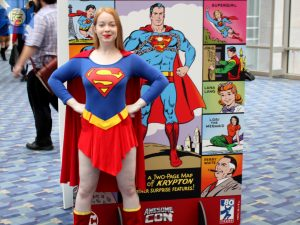 A fan poses with one of the display stands commemorating the Man of Steel.