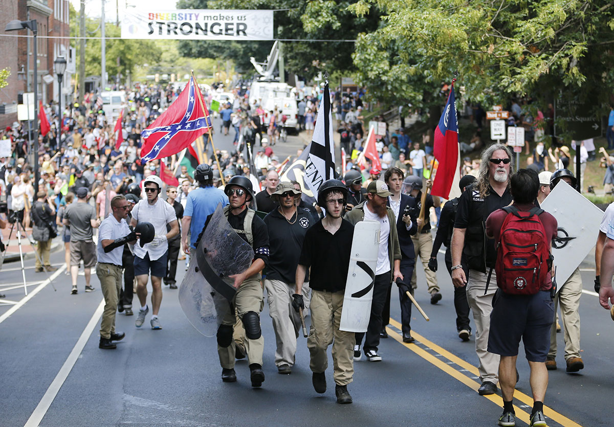 White nationalist demonstrators walk through town after their rally was declared illegal near Lee Park in Charlottesville, Va., Saturday, Aug. 12, 2017. (AP Photo/Steve Helber)